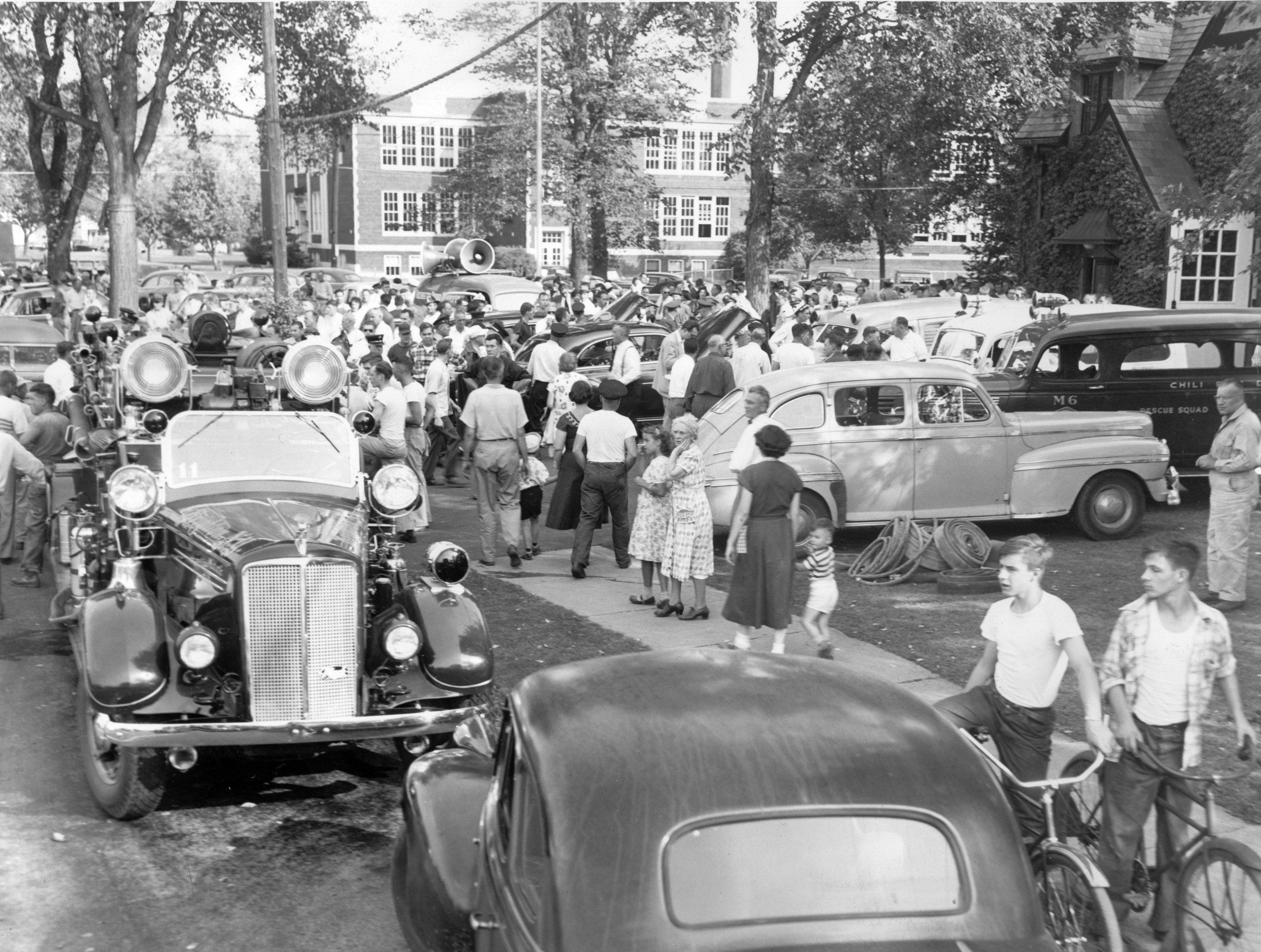 1951: Brighton residents gather near 12 Corners to hear announcements from authorities via loudspeakers on police cars after a string of gas explosions and fires ripped through Brighton neighborhoods. The incident left 3 dead and dozens without a place to live.