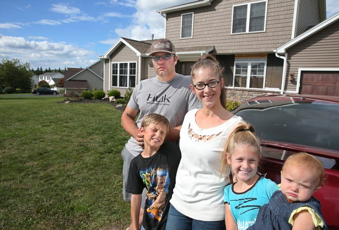 Jennifer McCann, and husband Dustin McCann, along with their kids, Skylar, 11 months, far right, Clayton Knowles, 9, and Analisa Knowles, 9, pose outside Jennifer's parents house in Webster Friday, Sept. 14, 2018.  The family drove up from North Carolina to flee Hurricane Florence.