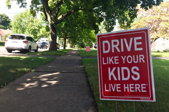 Signs posted in yards along Torrington Drive in Brighton command drivers to slow down, though residents say the signs are entirely ineffective.