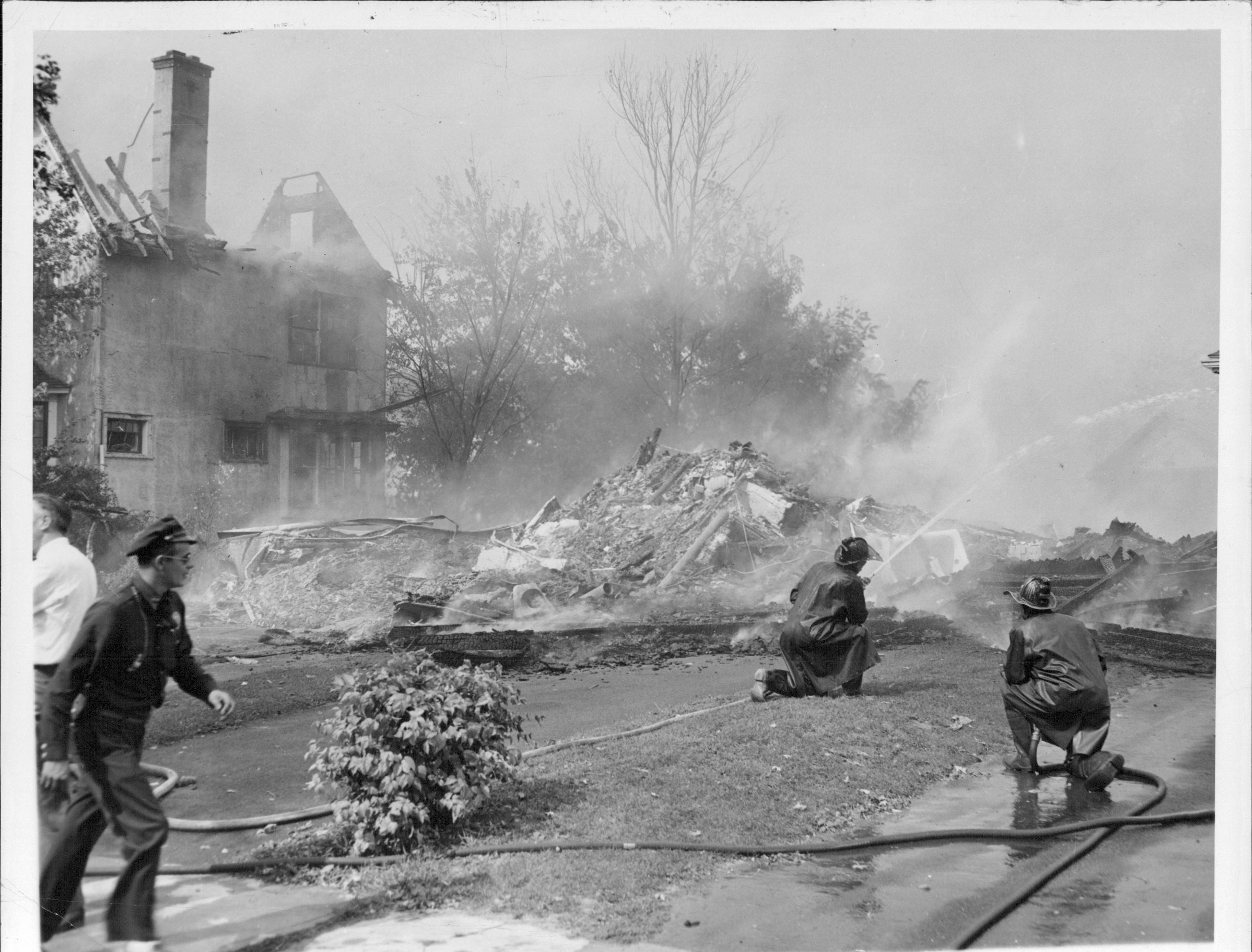 Firefighters spray water on remains of destroyed home.  (Staff photo, 9/21/1951)