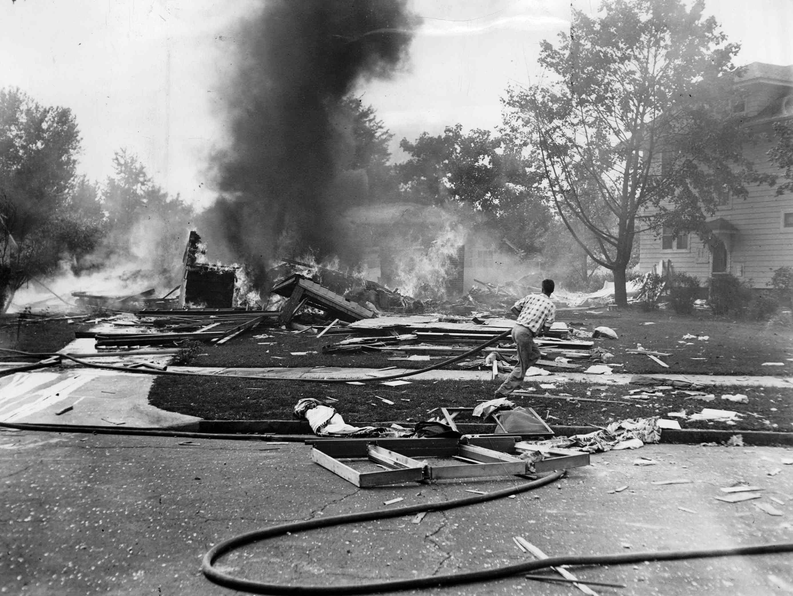 Only curling smoke and scattered household goods remain from this home on Fair Oaks Avenue. (Staff photo, 9/21/1951