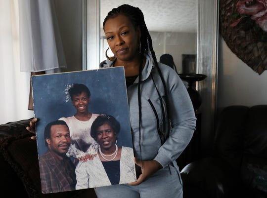 Lutheta Younger, 44, holds a photo of herself with father, Luther Younger, and mother, Waverlee Younger. Lutheta is caring for her ailing mother at home and has been handling the growing interest in her father's story, in which he claims to be 99 years old and a former Marine who fought in the Korean War despite an abundance of evidence to the contrary.