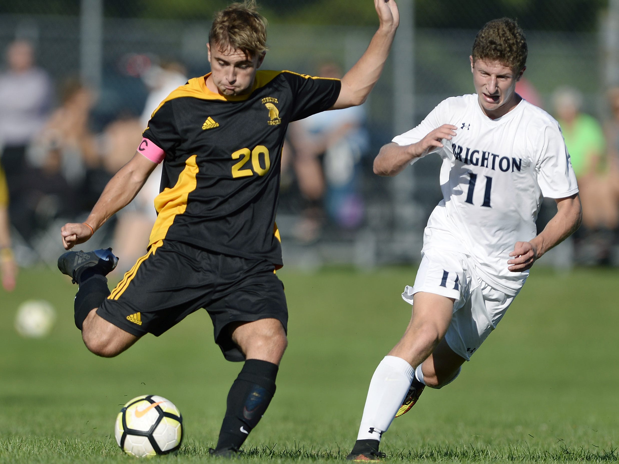 Greece Athena's Dylan Rice, left, winds up a shot on goal while defended by Brighton's Sam O'Connor during a regular season game played at Greece Athena High School, Thursday, Sept. 13, 2018. Greece Athena beat Brighton 1-0.