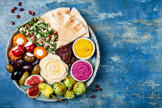 Middle Eastern Meze Platter With Green Falafel Pita Sun Dried Tomatoes Pumpkin And Beet Hummus Olives Stuffed Peppers Tabbouleh Figs Mediterranean Appetizer Party Idea