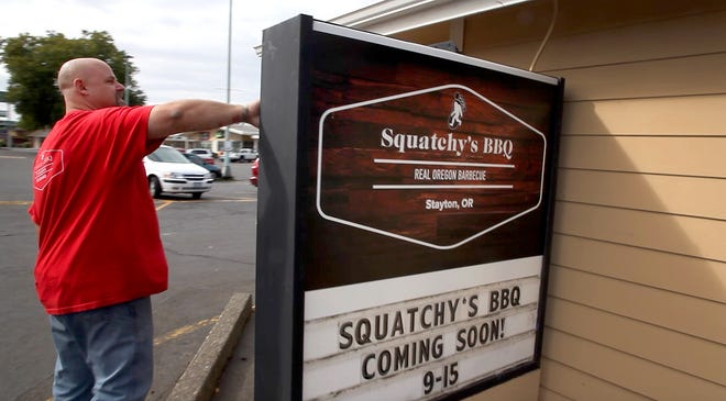 Squatchy's BBQ owner, Jason Lorraine takes a moment to look at his new sign outside of his new brick and mortar restaurant location in Stayton, Oregon, Thursday September 13, 2018. Just a few months since his original Squatchy's BBQ trailer burned, he is opening the new location thanks to the generosity of those who contributed through a Go Fund Me campaign set-up for Jason and his wife Julie following the fire.