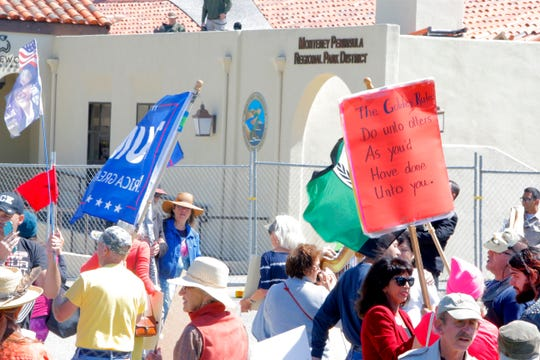 People wave signs at Palo Corona Regional Park in Monterey County, Calif. during a protest regarding a visit by Joe Arpaio, former sheriff of Arizona's Maricopa County. Arpaio was invited to speak at a Monterey Peninsula Republican Women Federated luncheon in Carmel Valley.