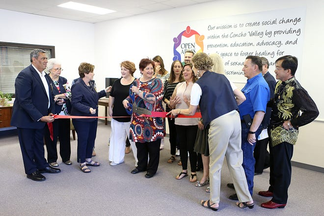 Karla Payne (Center), executive director of the Open Arms Rape Crisis Center+ LGBT+ Services gets ready to cut the ribbon during the non-profits open house Thursday, Sept. 13, 2018.
