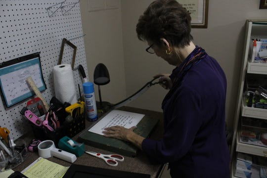 Sue Evans, owner of The Word Script, 2808 Sherwood Way, shaping a scripture to fit inside a frame.