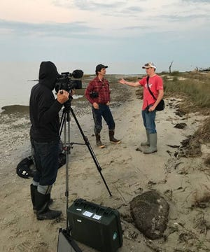 Tangier native Cameron Evans talks to a film crew from National Geographic about the island's culture and its erosion problems.