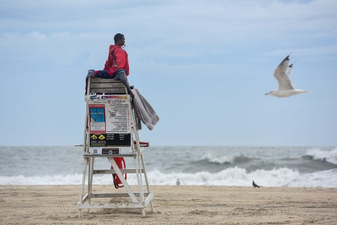 A lifeguard watches over a handful of beach goers at the inlet in Ocean City on Friday, Sept 14, 2018.