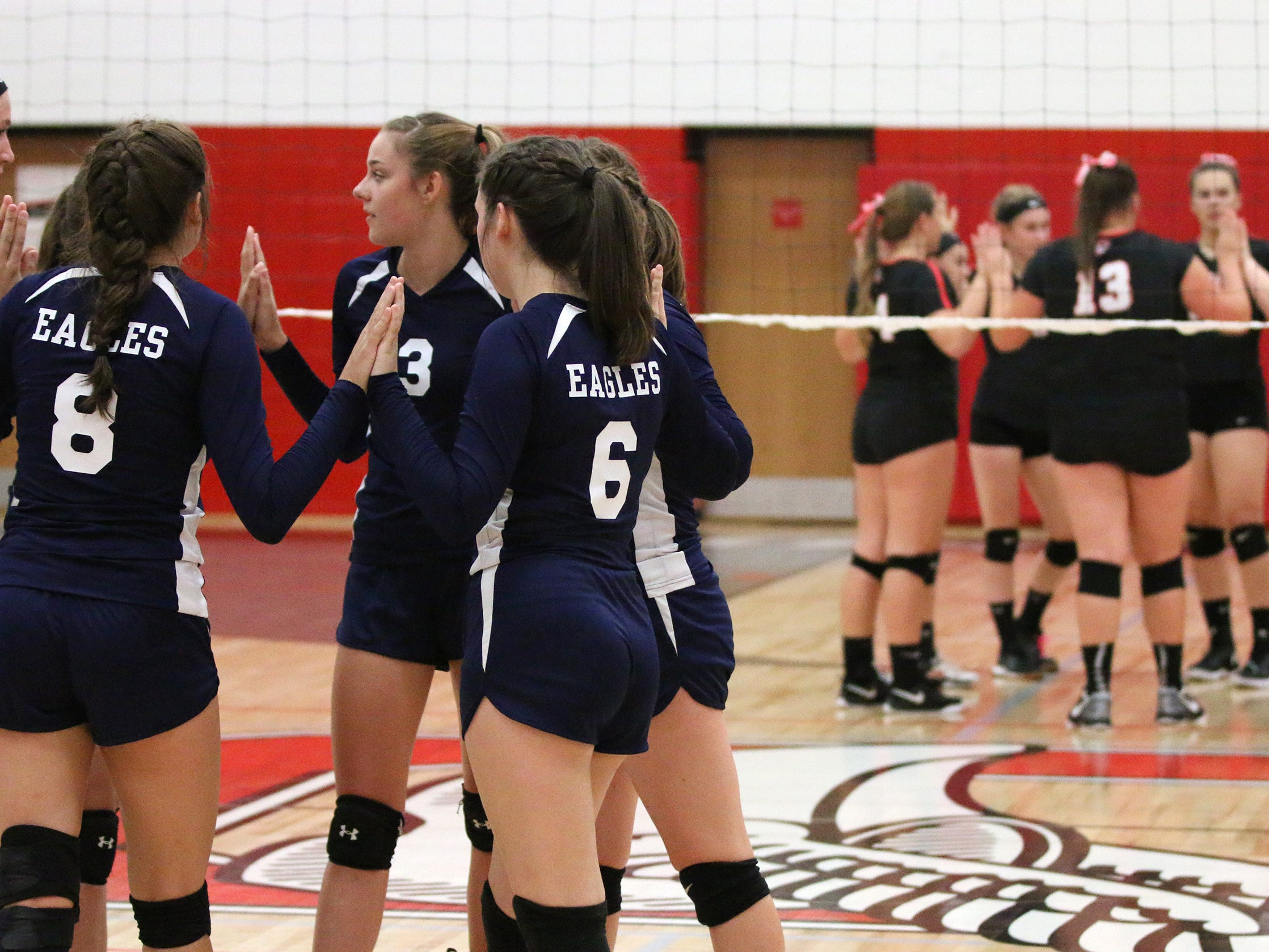 Sheboygan Christian, left, and Oostburg players huddle before action, Thursday, September 13, 2018, in Oostburg, Wis.