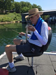 Jim Morris, 87, gives a small-mouth bass a 'kiss' before releasing it back to the waters of Table Rock Lake during a recent fishing trip. Morris and family celebrated 80 years in business at his Morris Loan and Investment company in late August.