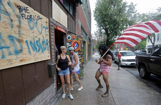 Jeff Egyp carries an American flag as he arrives at the Barbary Coast bar in downtown Wilmington, N.C., as the Florence threatens the coast Thursday, Sept. 13, 2018. (AP Photo/Chuck Burton)