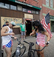 Jeff Egyp, right, and Brandon Fresin, left, park there bikes outside the Barbary Coast bar in downtown Wilmington, N.C., as the Florence threatens the coast Thursday, Sept. 13, 2018. (AP Photo/Chuck Burton)
