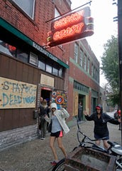 Two women that are riding out the storm dance to the music outside the Barbary Coast bar in downtown Wilmington, N.C., as the Florence threatens the coast Thursday, Sept. 13, 2018. (AP Photo/Chuck Burton)