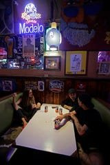 Kathryn Cloniger-Kirk, left, Michael Ussery, right, and Steven Harrington, back, chat as they relax at Barbary Coast bar in downtown Wilmington, N.C., as the Florence threatens the coast Thursday, Sept. 13, 2018. (AP Photo/Chuck Burton)