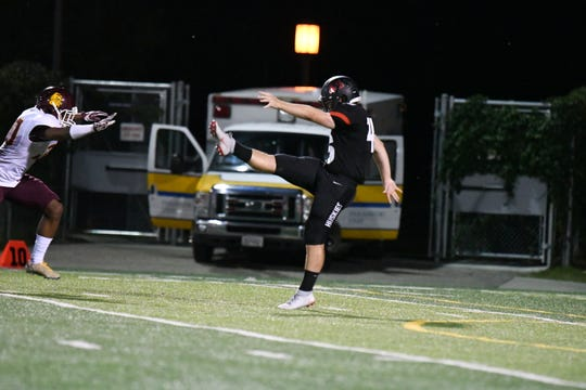 St. Cloud State's Adam Stage (right) punts in a game against Minnesota-Duluth Thursday at Husky Stadium. Stage, a sophomore, has added punting duties this season and averaged a season-best 37.7 yards against the Bulldogs.