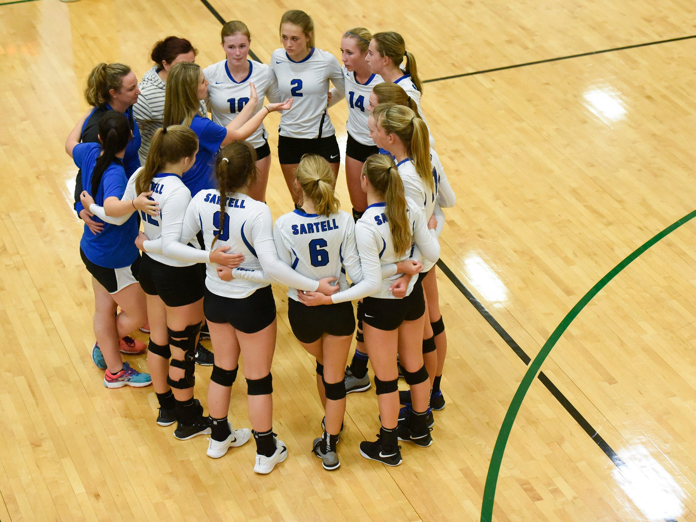 Sartell coaches and players talk between games.