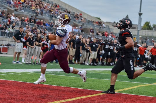Minnesota-Duluth running back Wade Sullivan (26) rushes into the end zone before St. Cloud State's Matthew Lechner (13) could get to him. It was a 3-yard touchdown run for Sullivan in the Bulldogs' 41-17 win at Husky Stadium.