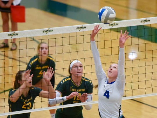 Sartell's Morgan Vosberg sets the ball at the net against Sauk Rapids during the first game Thursday, Sept. 13, at Sauk Rapids.