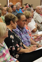 Crowd members listen carefully to Santa Clara residents opposed to a new development during a planning commission meeting Sept. 13, 2018.