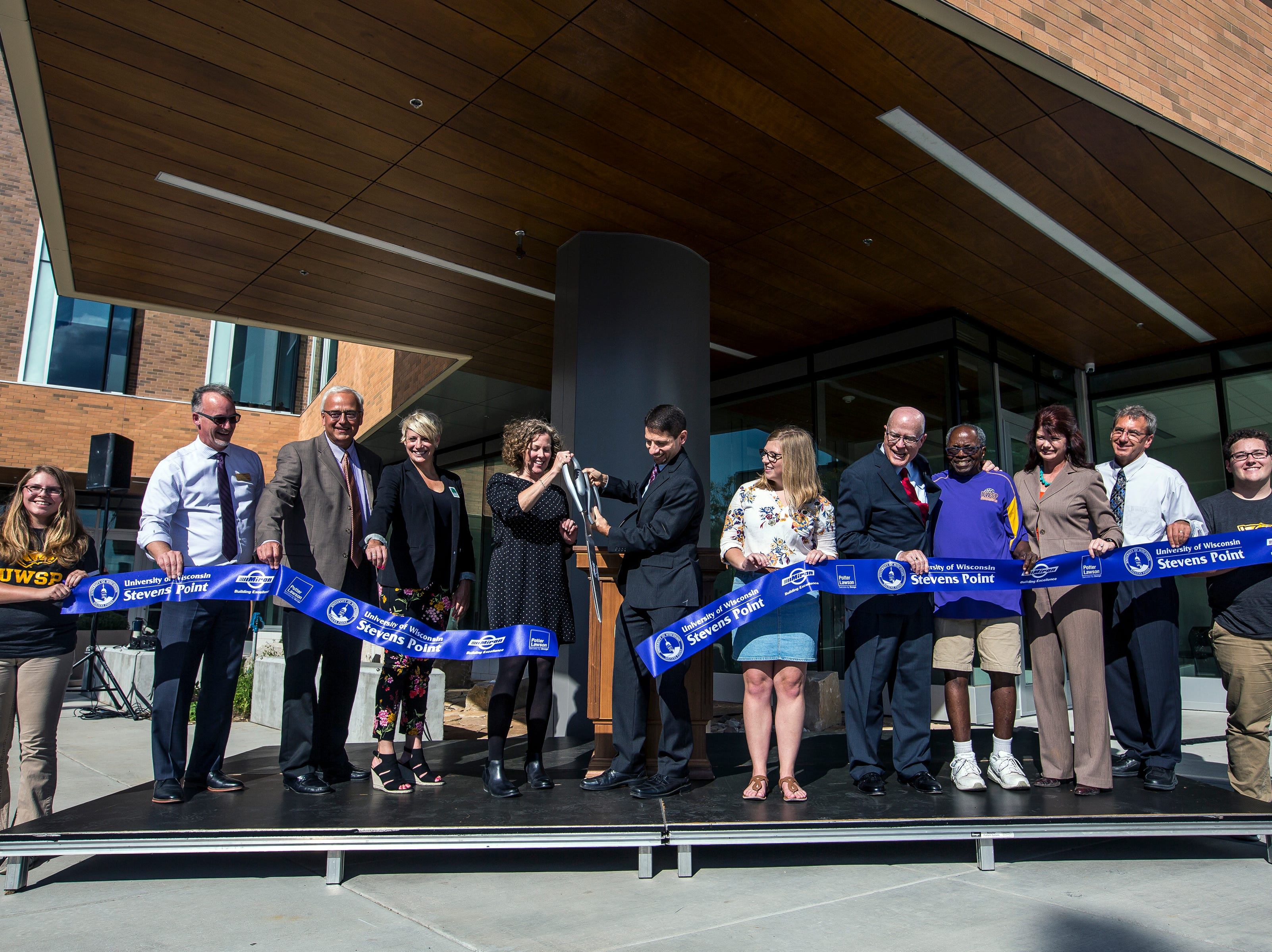 Representatives cut a ribbon during the opening ceremony for the Chemistry Biology Building at the University of Wisconsin-Stevens Point in Stevens Point, Wis., Sept. 14, 2018.