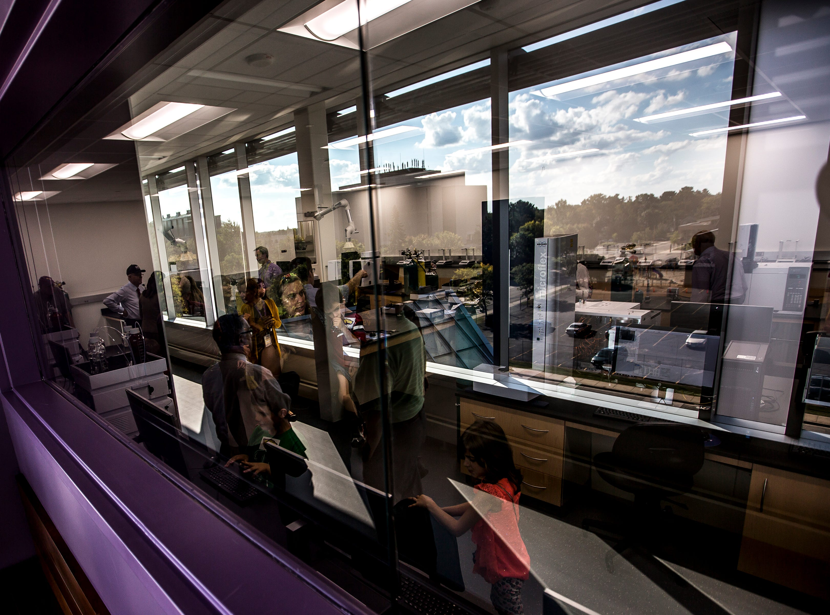 Views from a window is reflected in the windows of a laboratory as attendees tour its features during a tour of the Chemistry Biology Building at the University of Wisconsin-Stevens Point in Stevens Point, Wis., Sept. 14, 2018.
