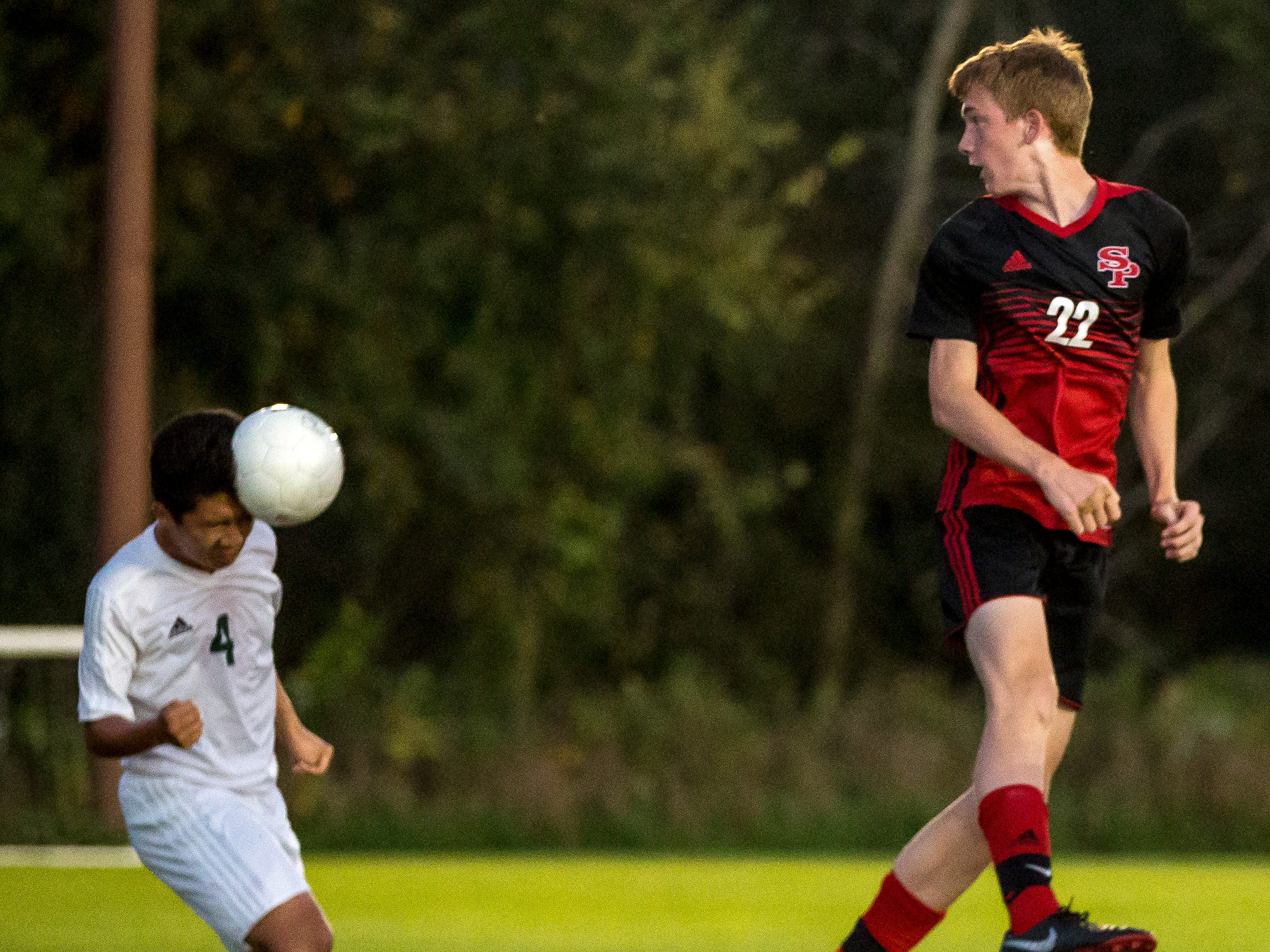 D.C. Everest player Chersa Lo heads the ball as SPASH's Jake Williams jumps to block it during a soccer game between SPASH and D.C. Everest in Stevens Point, Wis., September 13, 2018.