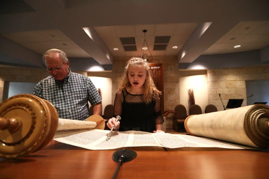 Rabbi Jack Romberg of Temple Israel helps Anya Byrne practice for a High Holy Day Torah reading last year.