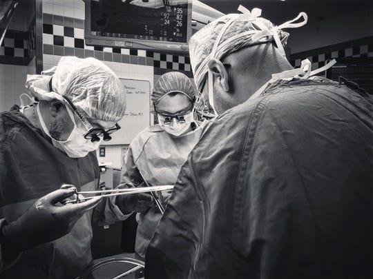 Dr. Aleksandr Reznichenko, left, takes part in a liver transplant operation in 2017 at the University of Cincinnati Medical Center.
