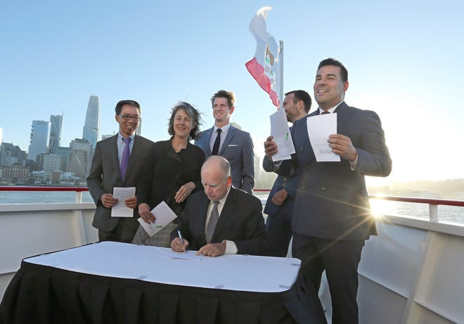 State Sen. Ricardo Lara, right, displays bills signed by Gov. Jerry Brown during a ceremony Thursday in San Francisco. Brown signed bills aimed at easing global warming during a cruise aboard the high-tech battery-operated San Francisco Bay sightseeing boat, Enhydra. Along with Lara, Brown was flanked by Democrats, Assemblyman Ed Chau, left, and Senators Nancy Skinner, Henry Stern, third from left and Ben Allen, second from right.