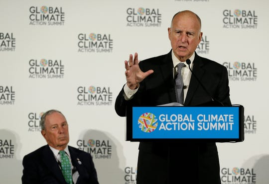 California Gov. Jerry Brown speaks as Michael Bloomberg, left, listens during a news conference at the Global Action Climate Summit on Thursday in San Francisco.