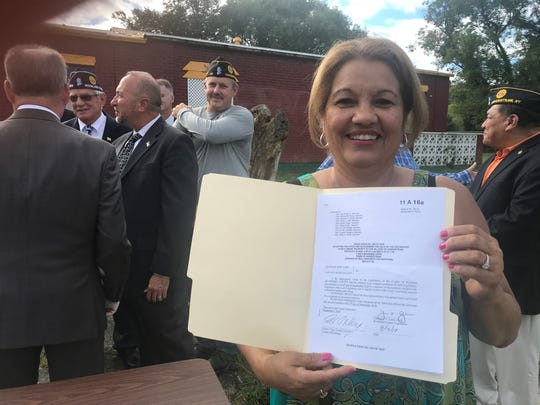 Yolanda Lopez, whose son Manny died in 2005 in Operation Iraqi Freedom, holds the resolution that allowed the Village of Haverstraw to buy a home for American Legion Post 46 from the county.