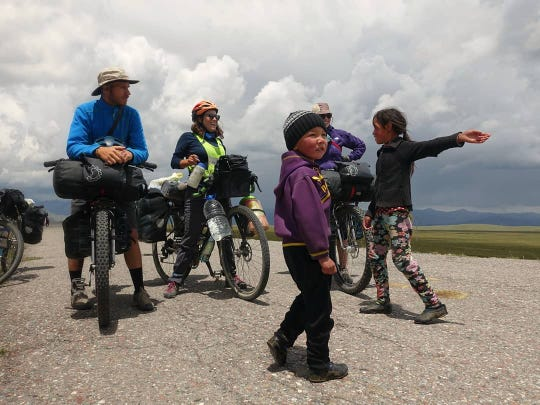 "Jay Austin and Lauren Geoghegan were on their way to the Kyrgyzstan border, when some kids stopped them to see if they wanted some hot tea, fresh bread or a rest in the nearby yurt. ""With a storm brewing on the horizon, we were all too happy to duck for cover and spend a little time with this lovely family,"" Austin wrote on Instagram."