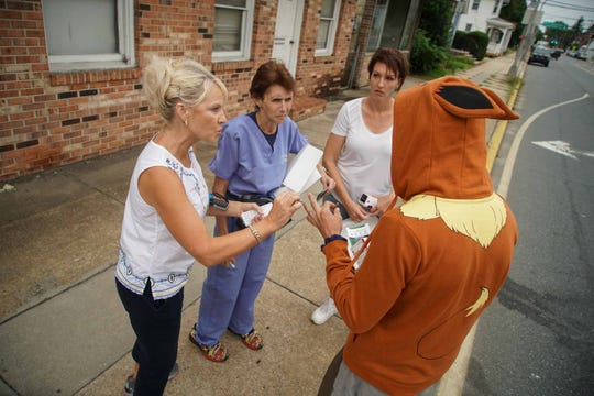 Lt. Gov. Bethany Hall-Long hands out information on addiction help with Dr. Sandra Gibney and Holly Rybinski, an outreach worker for Brandywine Counseling, while canvasing an area of Dover known for overdose deaths.