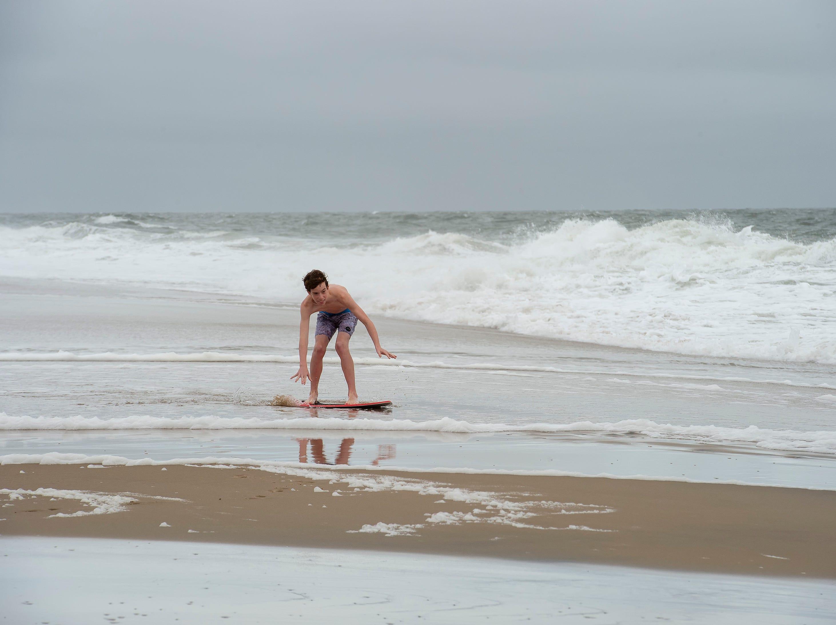 Ben Hess (13) of Leesburg, Va., rides his skim board at Bethany Beach after Hurricane Florence made landfall in North Carolina.