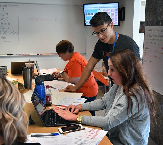 Michael Olaya, founder of Dexter Learning, talks with Jennifer Tanksley, a teacher a Sheppard Elementary, during a training session on computer coding Friday.