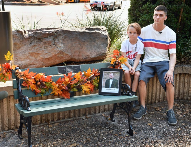 Harper Shobert, left, and Baylee Meacham, grandsons of the late Lynn Marshall, are photographed next to the park bench dedicated Thursday afternoon in memory of Marshall.