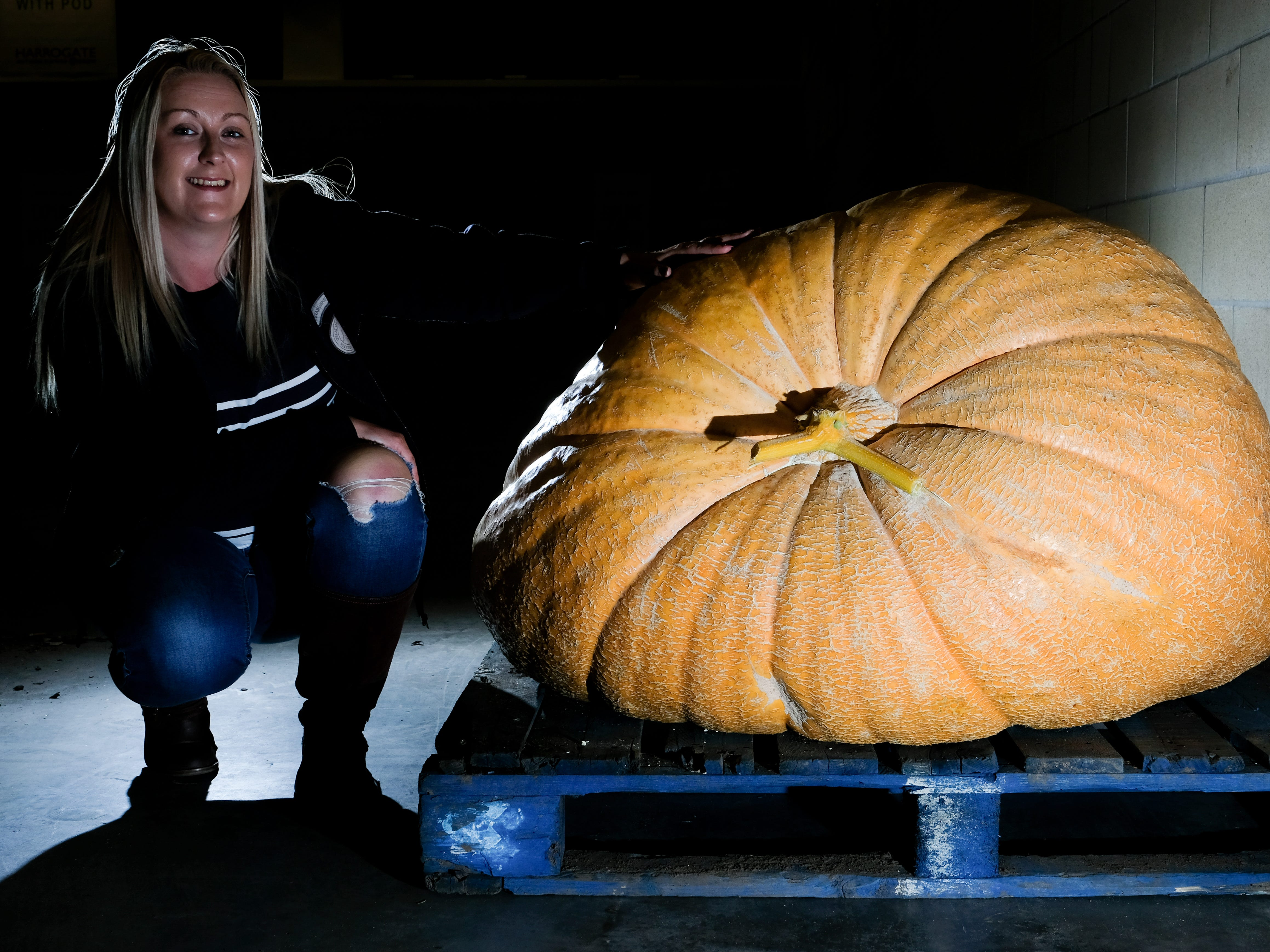 Laura Litchfield poses next to her giant pumpkin.