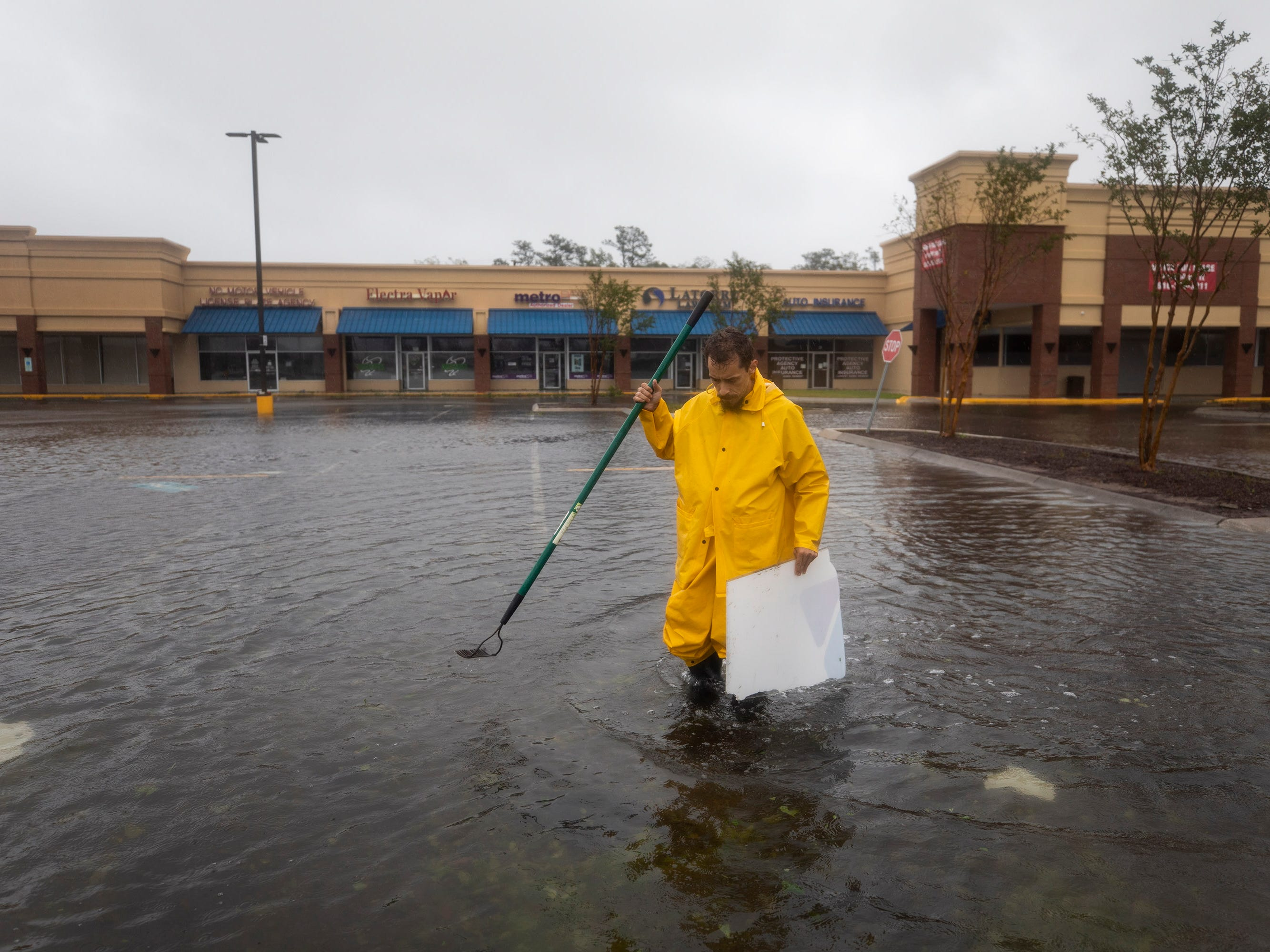 Jason Prevatte attempts to clear debris from a storm drain as Hurricane Florence comes ashore in Wilmington, N.C. Sept. 14, 2018.