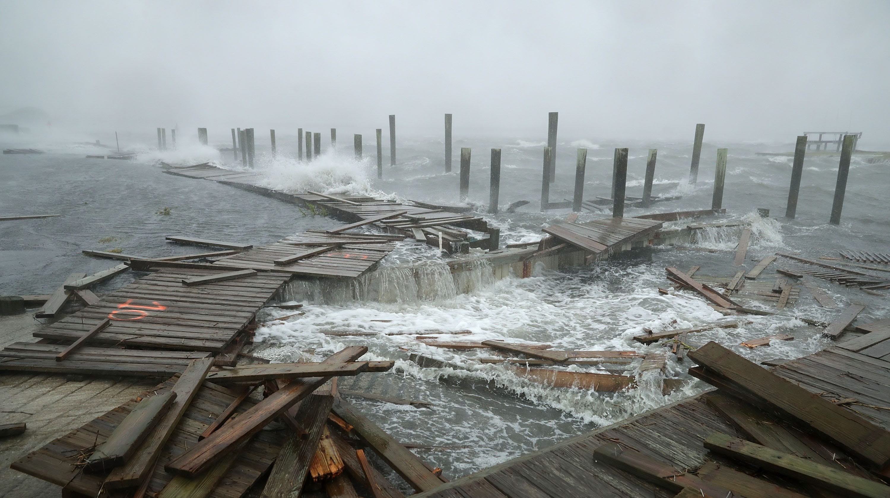 Portions of a boat dock and boardwalk are destroyed by powerful wind and waves as Hurricane Florence arrives September 13, 2018 in Atlantic Beach.