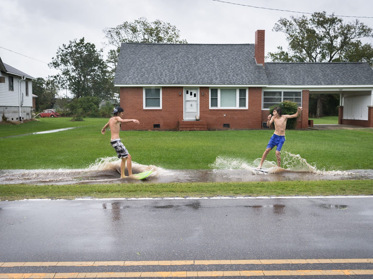 Deacon Etheridge, 14, left and Fortino Beltran, also 14, surf on a large puddle on Main Street in Swan Quarter, N.C.