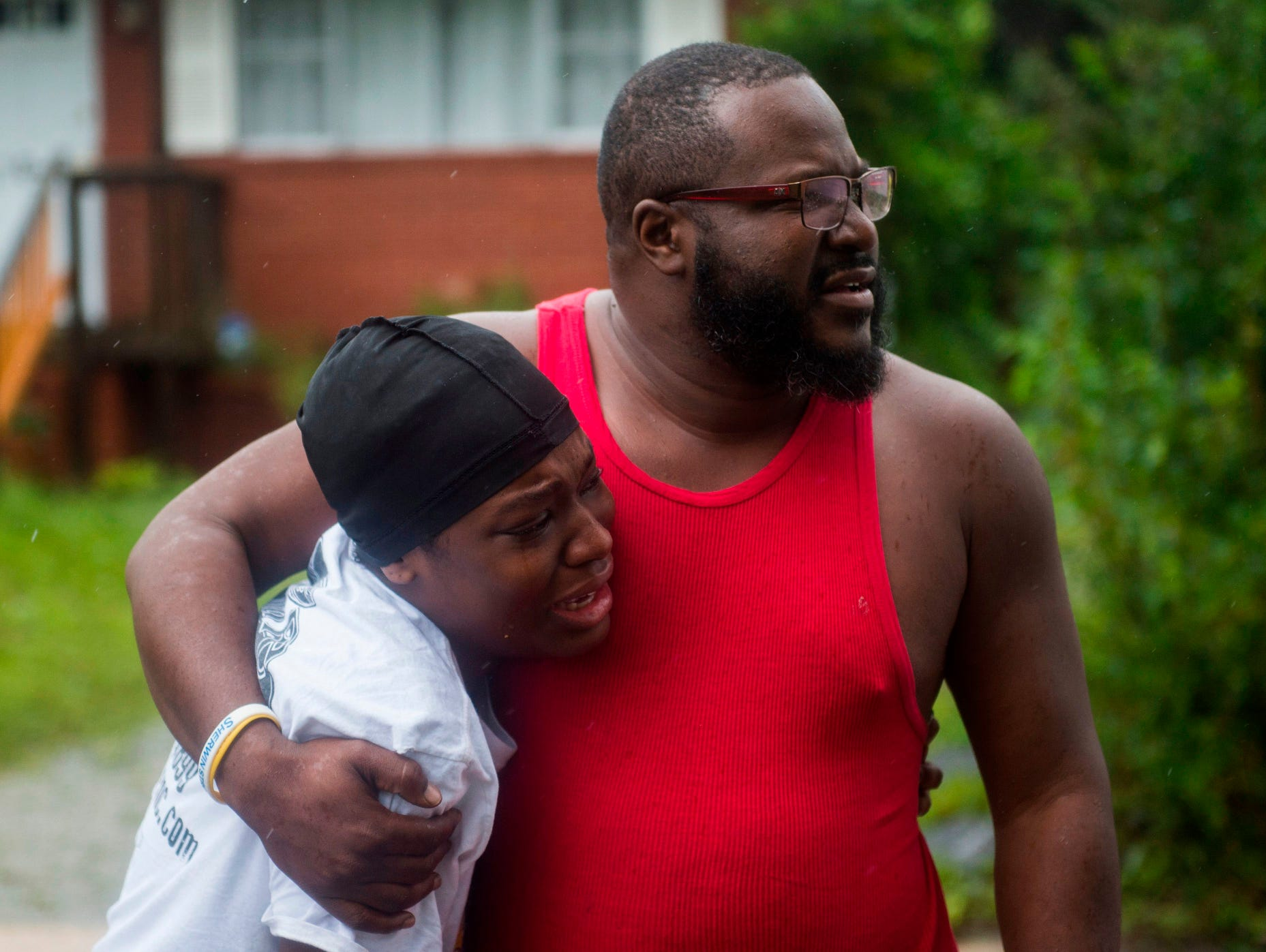A father and daughter learn that friends were injured in a house that a tree fell on during landfall of Hurricane Florence, in Wilmington, North Carolina on Sept.14, 2018. - Florence smashed into the US East Coast Friday with howling winds, torrential rains and life-threatening storm surges as emergency crews scrambled to rescue hundreds of people stranded in their homes by flood waters.