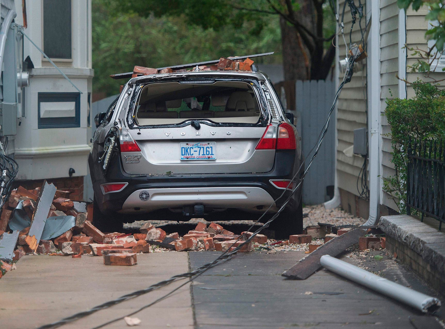 A car is destroyed from falling bricks as Hurricane Florence passes over Wilmington, N.C., Friday.  Florence smashed into the US East Coast Friday with howling winds, torrential rains and life-threatening storm surges as emergency crews scrambled to rescue hundreds of people stranded in their homes by flood waters. Forecasters warned of catastrophic flooding and other mayhem from the monster storm, which is only Category 1 but physically sprawling and dangerous.