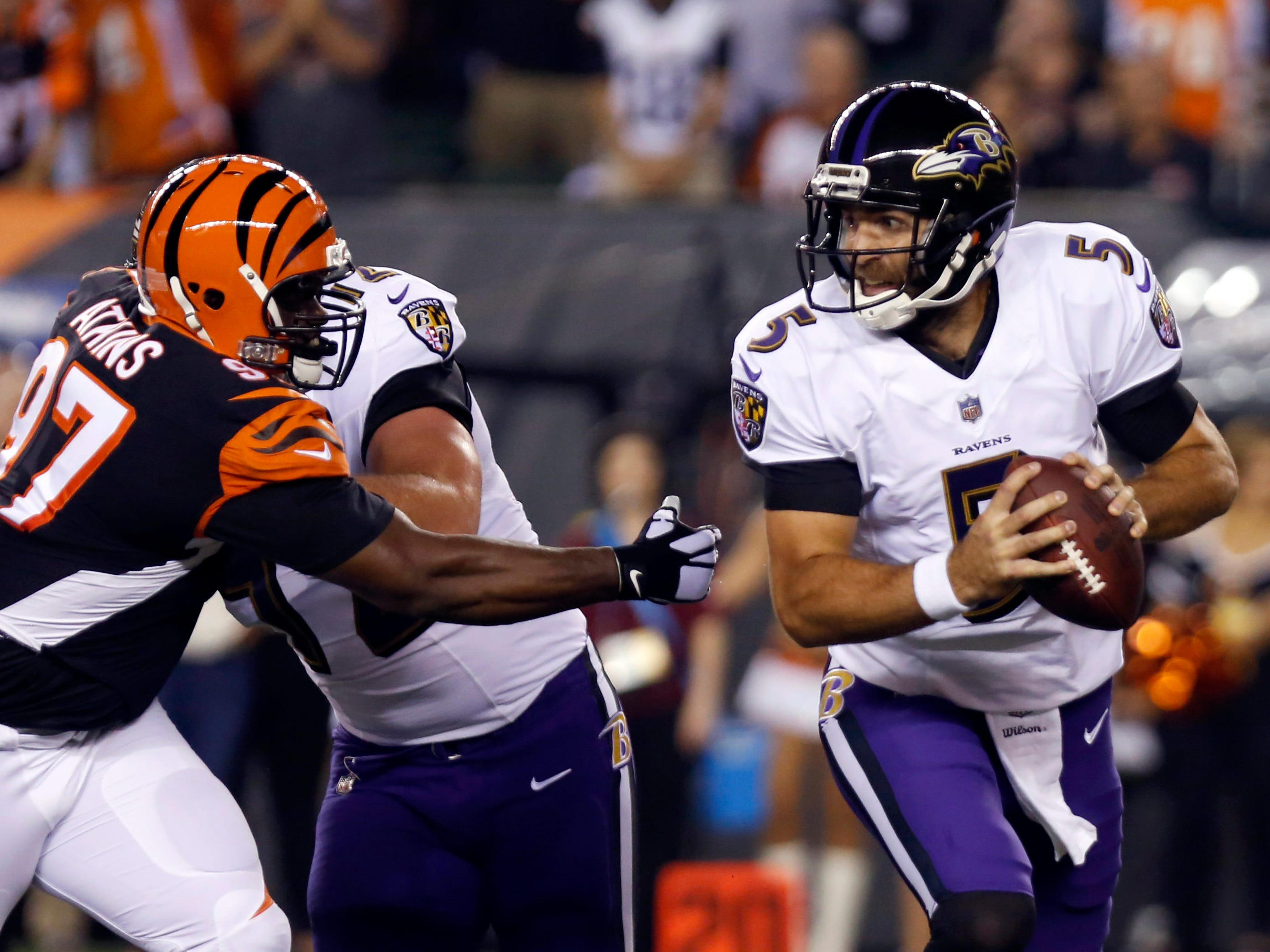 Baltimore Ravens quarterback Joe Flacco runs against Cincinnati Bengals defensive tackle Geno Atkins during the first half at Paul Brown Stadium.