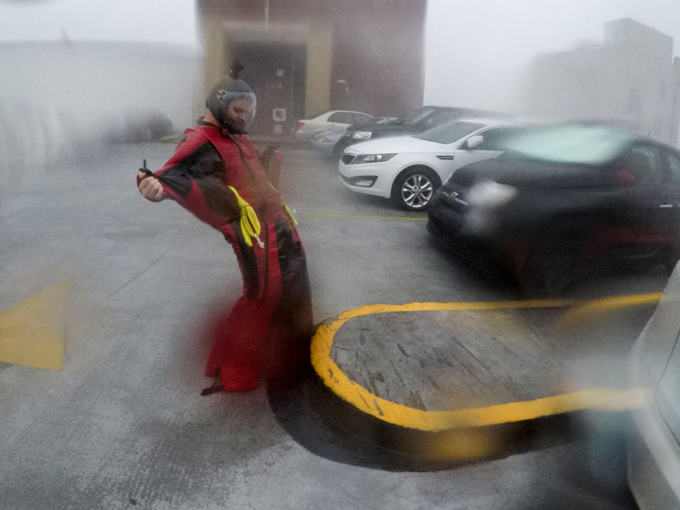 Michael Henderson a professional skydiver, stands on the seventh floor of a parking garage in downtown Wilmington, N.C.  as Hurricane Florence just hit land, Sept. 14, 2018.
