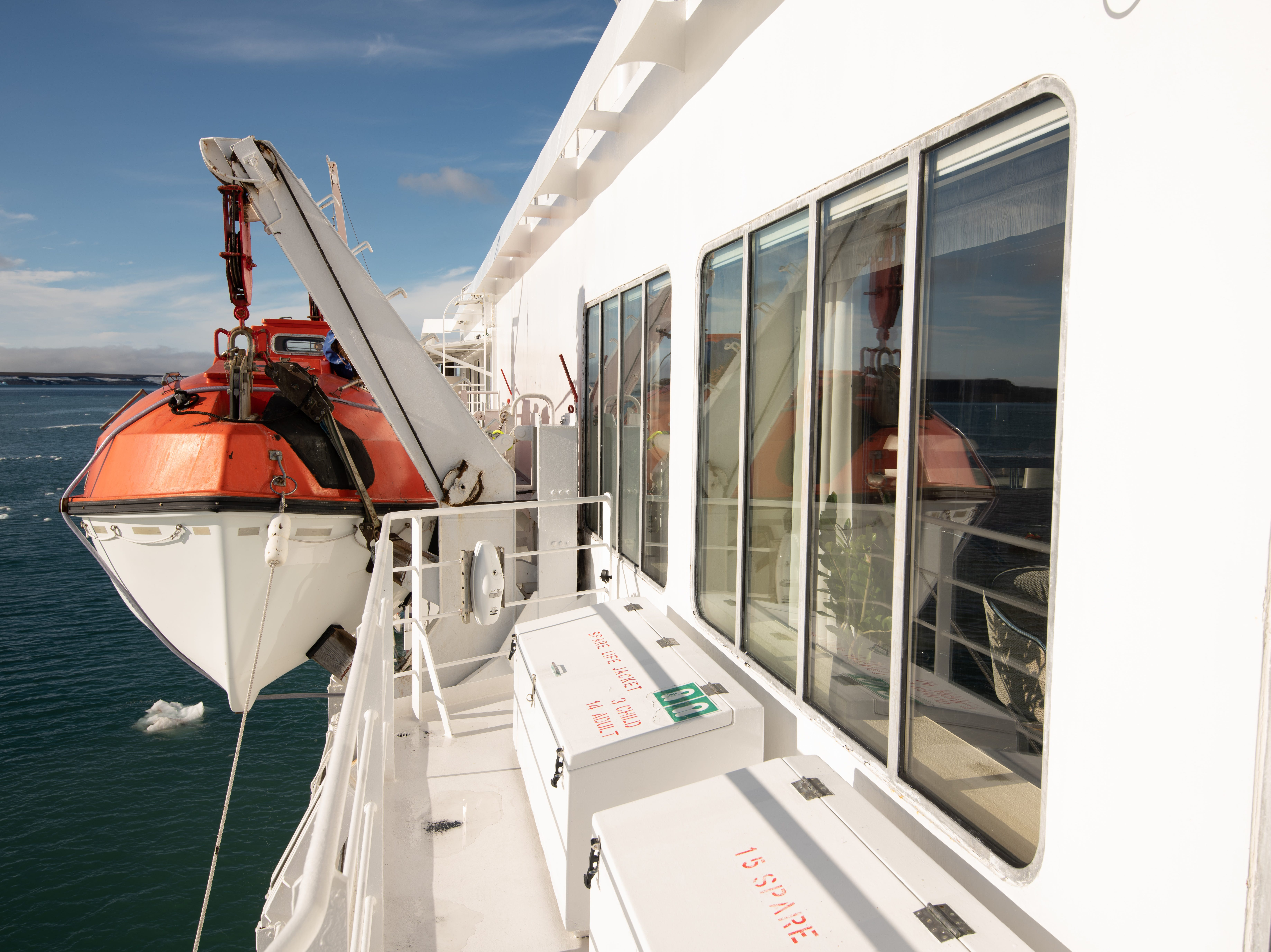 The exterior viewing area on Deck 7 wraps around the side of the ship to points where the vessel's lifeboats are visible.