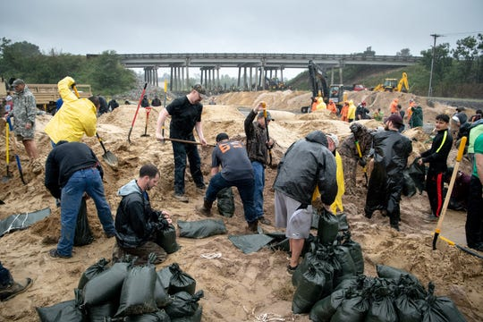 Volunteers fills sandbags to reinforce a low-lying area as Hurricane Florence approaches Lumberton, N.C., Friday.