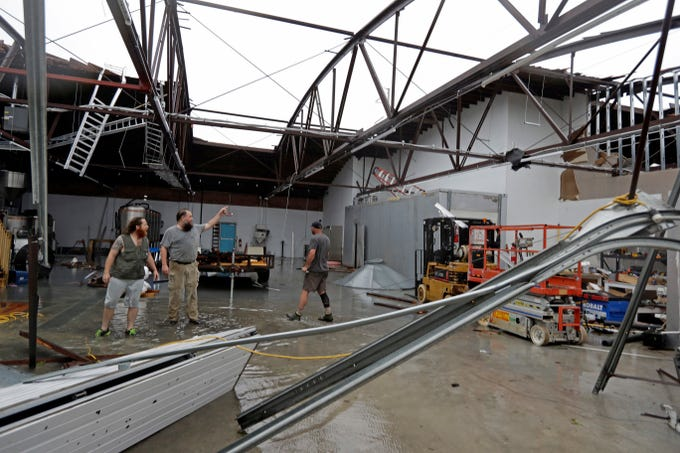 Ethan Hall, right, Michael Jenkins, center, and Nash Fralick, left, examine damage to Tidewater Brewing Co. in Wilmington, N.C., after Hurricane Florence made landfall  Sept. 14, 2018.
