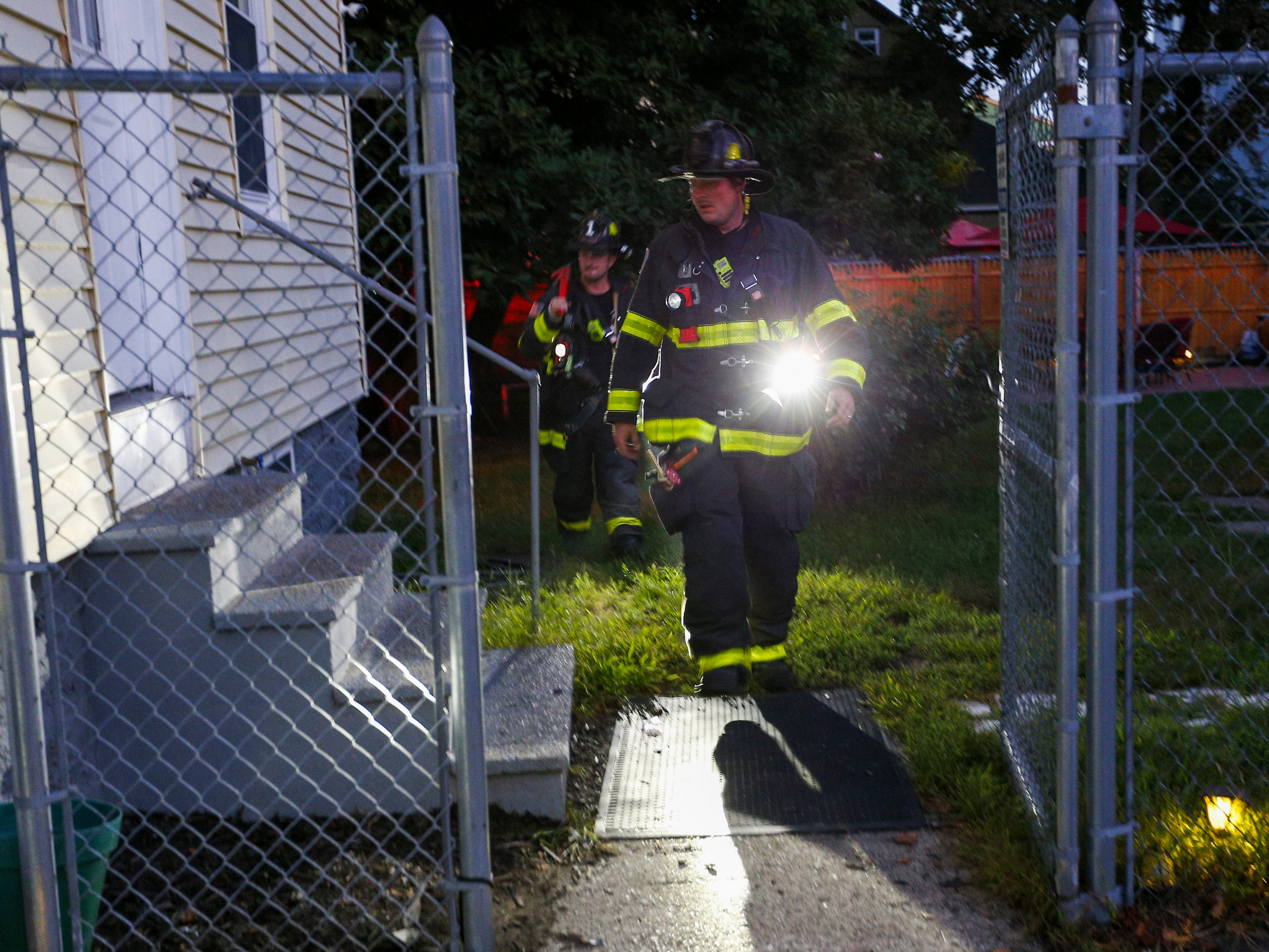 Firefighters search for a way into a house to check the gas line in Lawrence, Mass. on Sept. 13, 2018. A series of reported gas explosions in towns north of Boston Massachusetts set homes ablaze and forced the mandatory evacuation of residents.